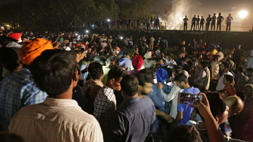 People and police gather at the site of a deadly train accident in Amritsar, India.