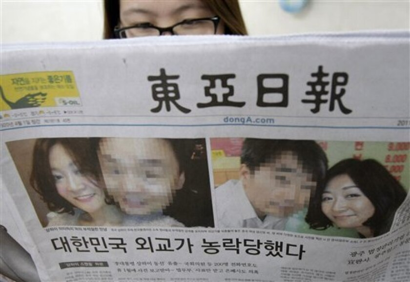 """A South Korean woman reads a newspaper with photos showing a Chinese woman named Deng Xinming poses with South Korean diplomats, in Seoul, South Korea, Wednesday, March 9, 2011. South Korea's Foreign Minister Kim Sung-hwan has offered a public apology over an alleged sex scandal involving several diplomats and the Chinese mistress. The headline read, """"South Korean Diplomacy fell a prey to the lust."""" (AP Photo/Ahn Young-joon)"""