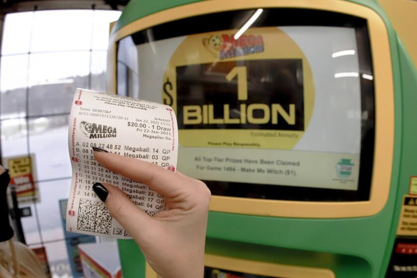 Una mujer muestra un boleto para la lotería Mega Millions
