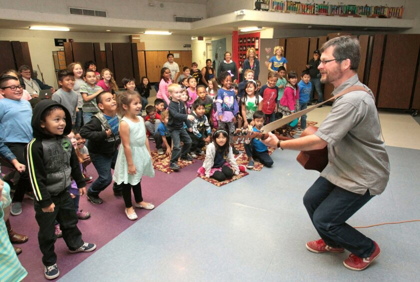 """Prominent children's book author Eric Ode performs his audience participation song """"Gophers in the Garden"""" to the delight of kids at Miller Elementary School this morning. The Assistance League of Inland North County funded his visit. The organization raises money through thrift shop sales to bring"""