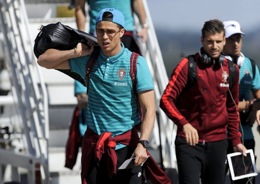 Portugal's soccer players Cristiano Ronaldo, foreground, with Miguel Veloso, centre, and Raul Meireles behind, walk down from a plane as they arrive at the Viracopos airport, in Campinas, Brazil, Tuesday, June 11, 2014. Portugal will play in group G of Brazil's 2014 soccer World Cup. (AP Photo/Paulo Duarte)