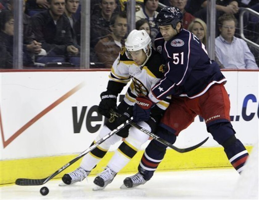 Columbus Blue Jackets' Fedor Tyutin, right, of Russia, and Boston Bruins' Chris Kelly chase a loose puck during the first period of an NHL hockey game Tuesday, March 15, 2011, in Columbus, Ohio. (AP Photo/Jay LaPrete)