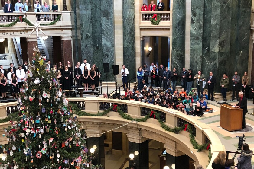 """Wisconsin Gov. Tony Evers prepares to light the Wisconsin Capitol tree that he calls a """"holiday tree"""" Friday, Dec. 6, 2019 in Madison, Wis. A choir sings songs including """"O Christmas Tree"""" and """"O Come All Ye Faithful"""" during the event. (AP Photo/Scott Bauer)"""