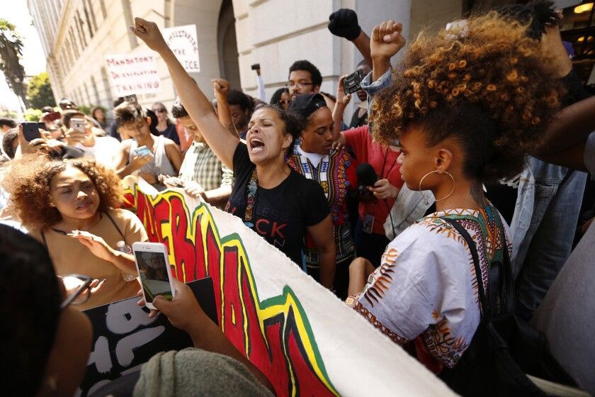 Melina Abdullah, a Cal State Los Angeles professor affiliated with the Black Lives Matter movement, center, chants after she is released by police after being detained inside Los Angeles City Hall.