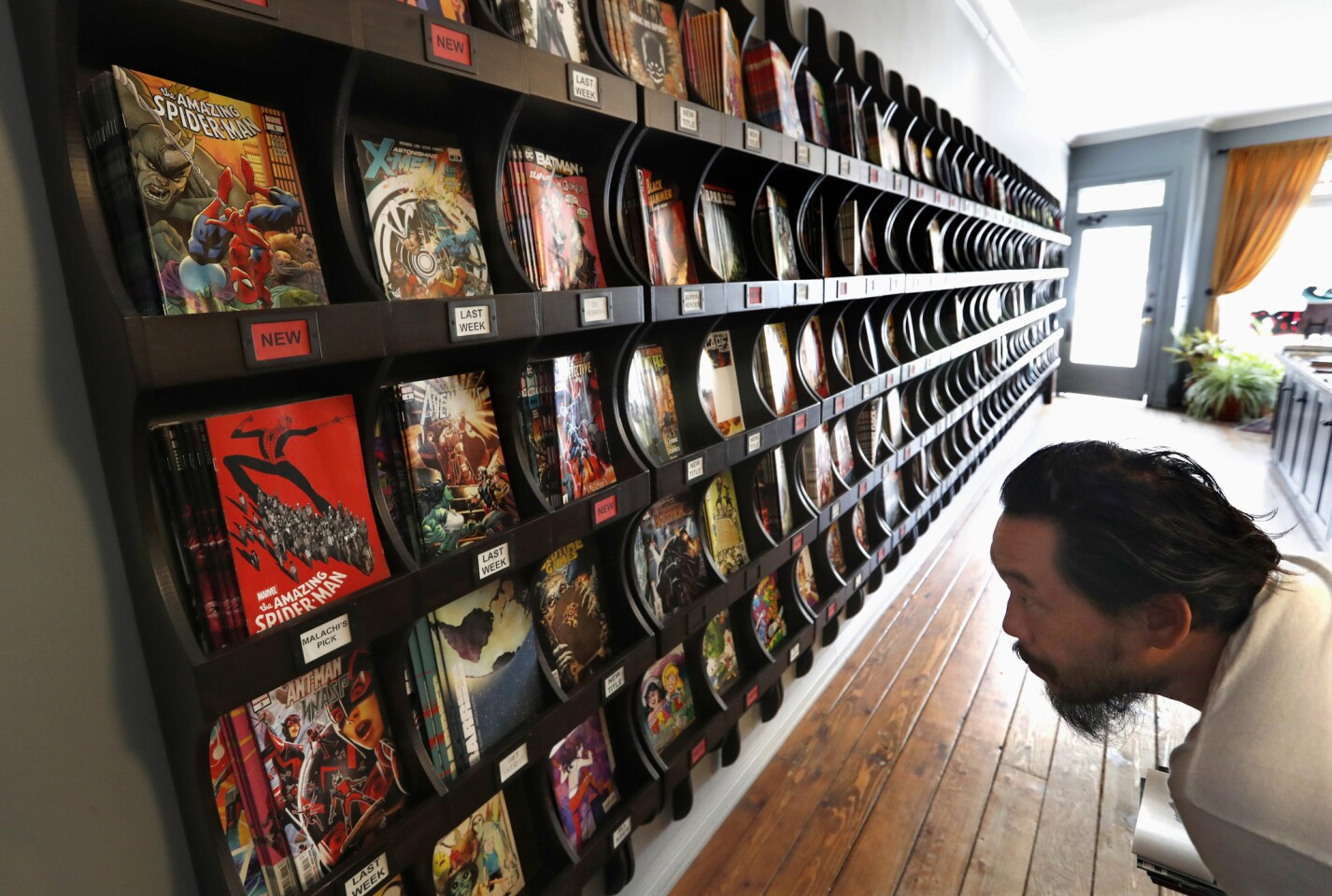 Artist David Choe of Koreatown looks at Marvel comic books for sale at Secret Headquarters on Sunset Boulevard in Los Angeles on July 11.