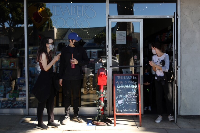 Customers wait outside a store with a sign advertising in-store browsing