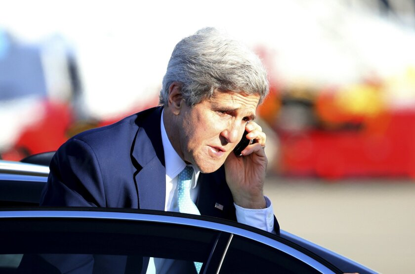 U.S. Secretary of State John Kerry talks on a mobile phone as he arrives at Sydney airport in Australia, Wednesday, Aug. 13, 2014. Kerry ended his visit in Australia for an annual Australia-United States Ministerial Consultations (AUSMIN) meeting. (AP Photo/Rob Griffith, Pool)