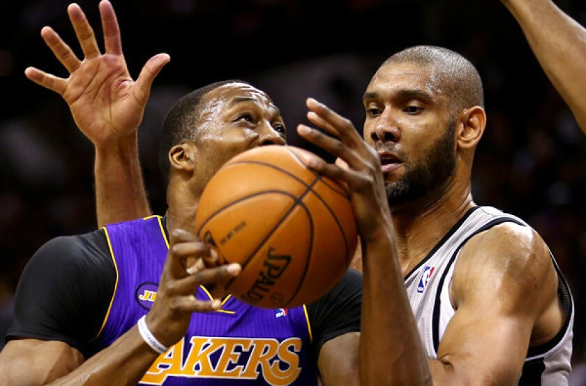Lakers center Dwight Howard tries to power his way past Spurs power forward Tim Duncan during Game 2 of their best-of-seven playoff series Wednesday night in San Antonio.