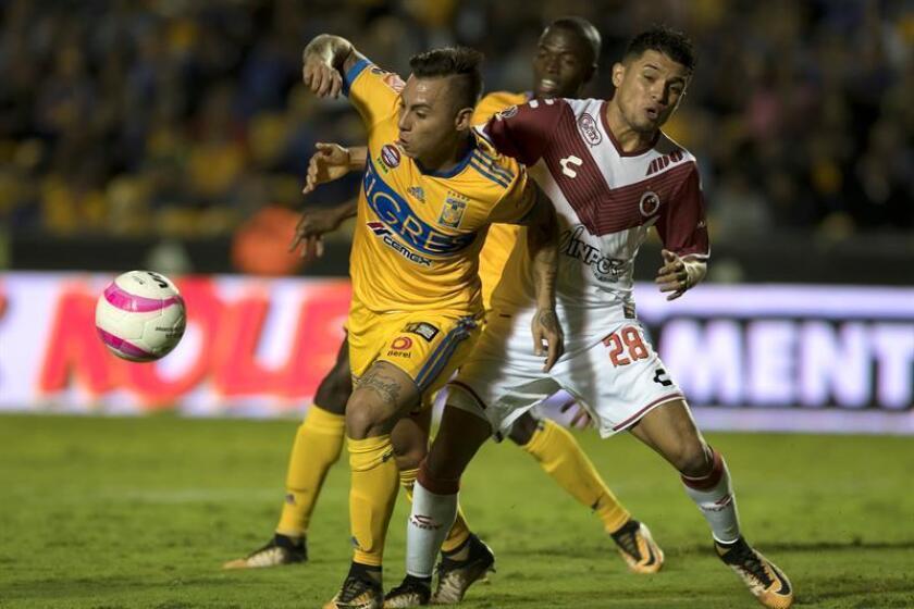 En la imagen un registro de Eduardo Vargas (i), delantero chileno de los Tigres de UANL, quien anotó el gol del empate 1-1 con el León de Guanajuato en el partido de ida de esta llave de cuartos de final del fútbol en México. EFE/Archivo