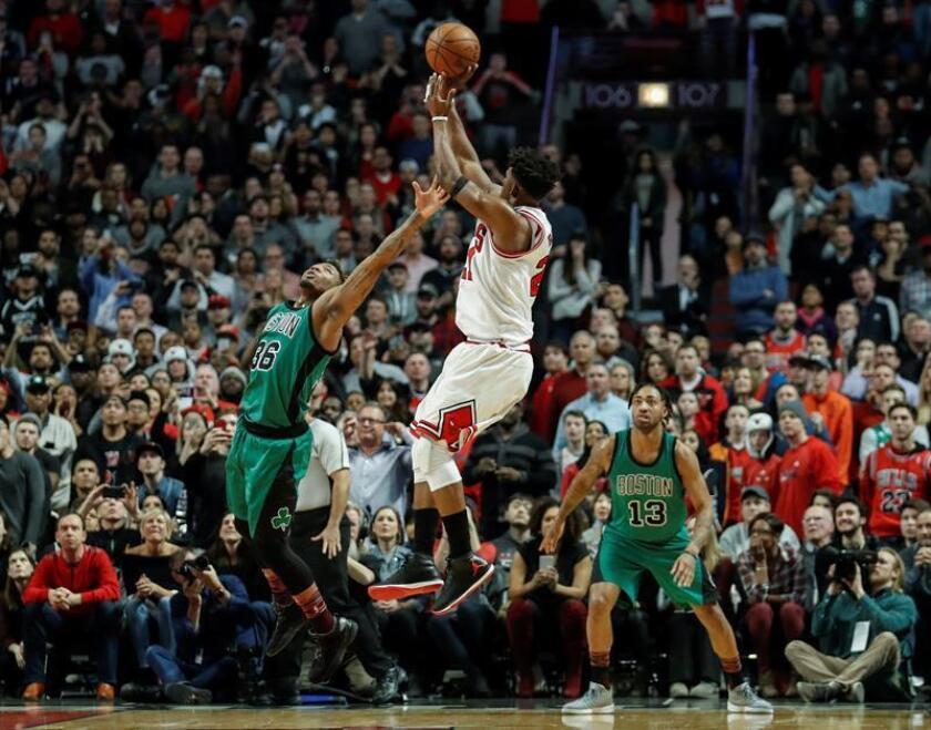 Jimmy Butler (c) de Bulls lanza sobre Marcus Smart (i) de Celtics, durante el juego de la NBA en el United Center en Chicago, Illinois (EE.UU.). EPA