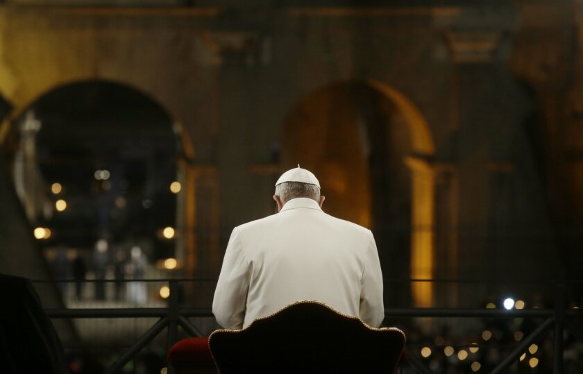 Pope Francis prays in front of the Colosseum at the start of the Via Crucis (Way of the Cross) torchlight procession celebrated by Pope Francis on Good Friday in Rome, Friday, April 3, 2015. (AP Photo/Gregorio Borgia)