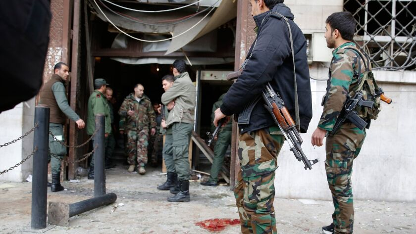 Syrian soldiers stand at the Palace of Justice in Damascus after a suicide bombing on March 15, 2017.