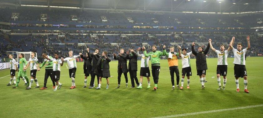 Moenchengladbach's team celebrates winning the German soccer cup second round match between FC Schalke 04 and Borussia Moenchengladbach  in Gelsenkirchen, Germany, Wednesday, Oct. 28, 2015. Schalke was defeated by Moenchengladbach with 0-2. (AP Photo/Martin Meissner)