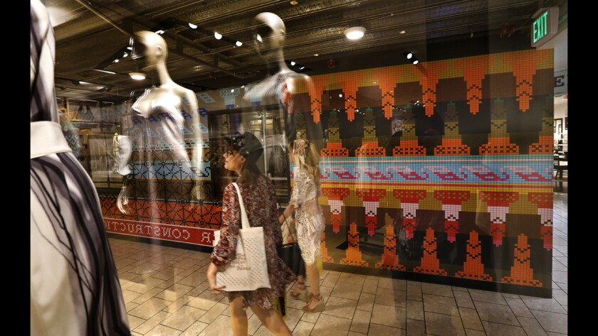 """Shoppers walk past a construction barricade, background, decorated with artwork by Lisa Anne Auerbach titled """"Strik Strikke, 2017,"""" on the sixth floor of the Beverly Center in Los Angeles on April 20, 2017. The artwork, a vibrant wallpaper, is composed of hundreds of sweater patterns. Auergach's work is part of a Beverly Center art project that's morphing along with the building's $500-million renovation."""