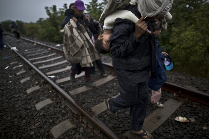 Bara'ah Alhammadi, 10, a Syrian refugee, is carried on the back of her father as they make their way along a railway track after they crossed the Serbian-Hungarian border near Roszke, southern Hungary, Friday, Sept. 11, 2015. (AP Photo/Muhammed Muheisen)