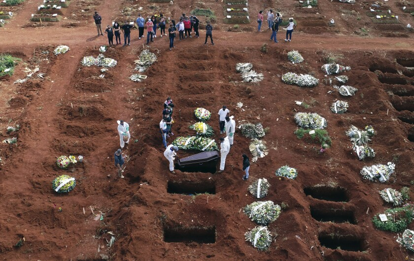 Workers lower a coffin into a grave.