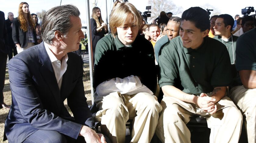 Gov. Gavin Newsom talks with Juan Cruz Lopez Jr. right, a youth inmate at the O.H. Close Youth Correctional Facility in Stockton.