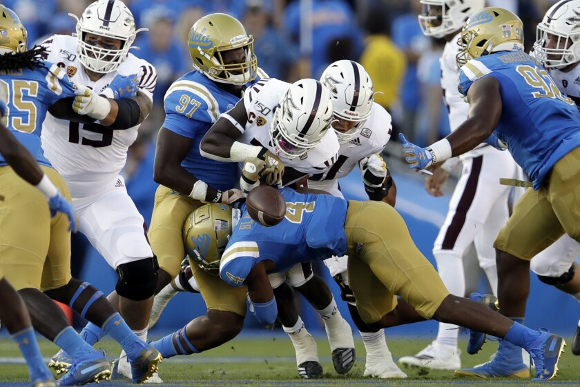 UCLA defensive back Stephan Blaylock forces Arizona State running back Eno Benjamin to fumble.