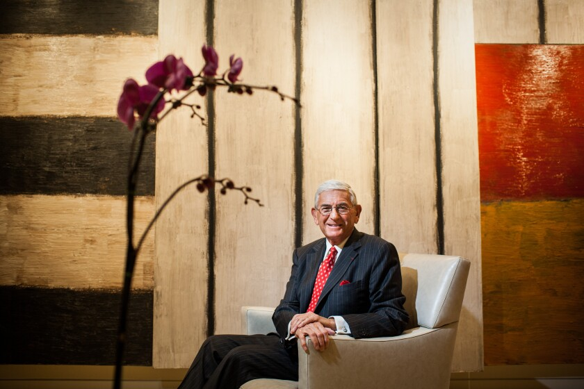 Eli Broad sits in a chair in front of an artwork