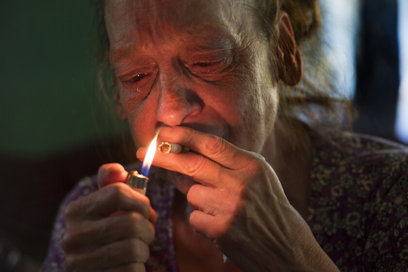 Fifty seven-year-old SheilaMcGlothlinsmokes while weeping over lack of money and her failing health in Grundy, Virginia, on May 26, 2017.