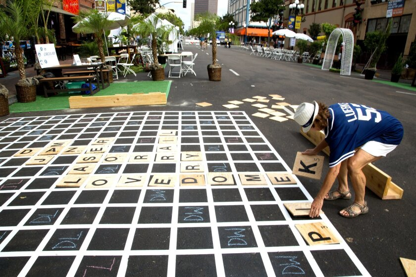 Cindy O'Grady from Clairemont engages in a competitive game of scrabble played out on a parking space on Fourth Avenue in the Gaslamp Quarter on Park(ing) Day.