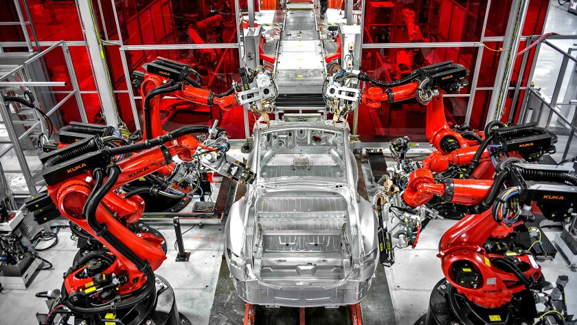 Robots assemble parts of a car at Tesla's factory in Fremont.