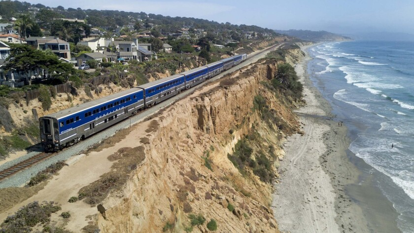 A Surfliner train travels along the fragile bluffs in Del Mar. Bluff collapses near the railroad tracks increased significantly last year, with four collapses from August to December. Officials are evaluating how to avoid incidents along this critical route.