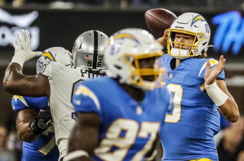 Chargers quarterback Justin Herbert passes under pressure by Las Vegas Raiders defensive tackle Darius Philon.