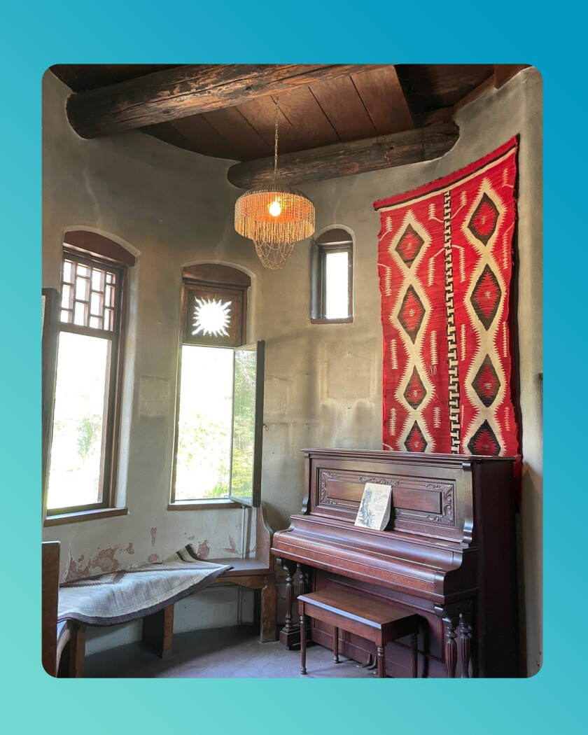 Room in the Lummis House with a piano and wall-hanging.