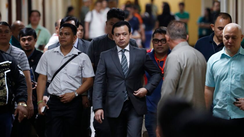 Philippine Sen. Antonio Trillanes IV, center, returns to the Senate building to hold a news conference after posting bail in Pasay, south of Manila, Tuesday.