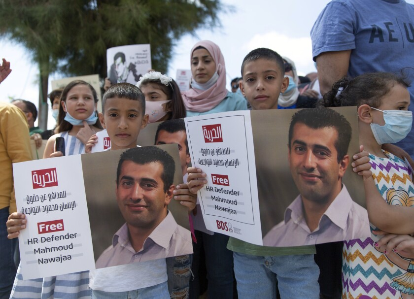 """Aws, 7, left, and Amr, 9, hold posters with a picture of their father, Mahmoud Nawajaa, a leading coordinator of the Palestinian-led boycott movement against Israel, BDS, during a protest calling for the EU to press for his release, in front of the German Representative Office, in the West Bank city of Ramallah, Tuesday, Aug. 11, 2020. The activist was arrested on July 30, remains in Israeli custody and has not been charged. Israel says the arrest is not connected to his boycott activities, and that he is is suspected of unspecified """"security offenses,"""" but boycott activists accuse Israel of fabricating the case in order to justify the arrest. (AP Photo/Nasser Nasser)"""