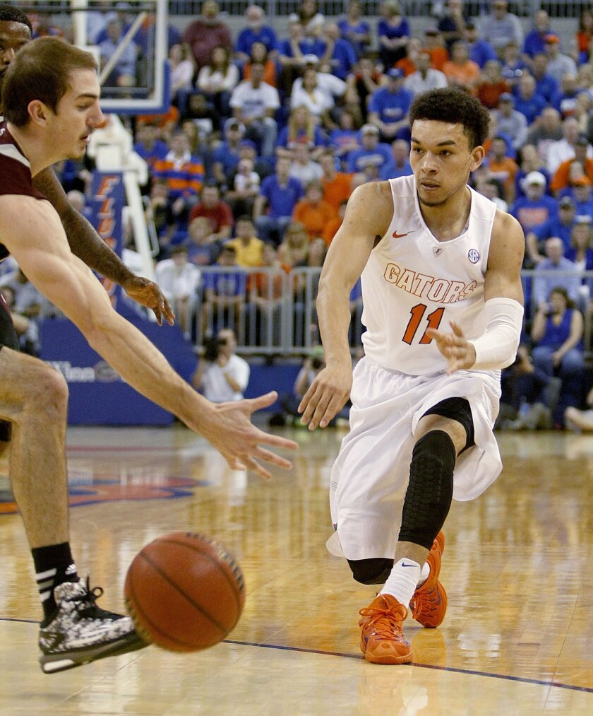 Florida guard Chris Chiozza (11) passes around Texas A&M guard Alex Caruso during the first half of an NCAA college basketball game Tuesday, March 3, 2015, in Gainesville, Fla. (AP Photo/The Gainesville Sun, Matt Stamey)