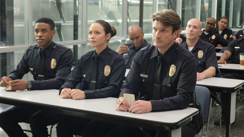 "Titus Makin, left, Melissa O'Neil and Nathan Fillion in the squad room of ABC's new series ""The Rookie."""