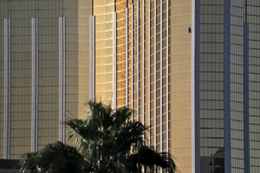 A curtain hangs out of a broken window, upper right, at Mandalay Bay on Oct. 2, 2017, the morning after a mass shooting on the Las Vegas Strip.