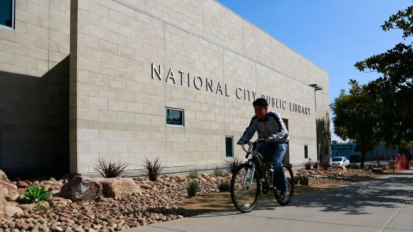 A bicyclist travels past the National City Public Library. The city wants to create neighborhoods that allow residents to bike or walk to destinations.