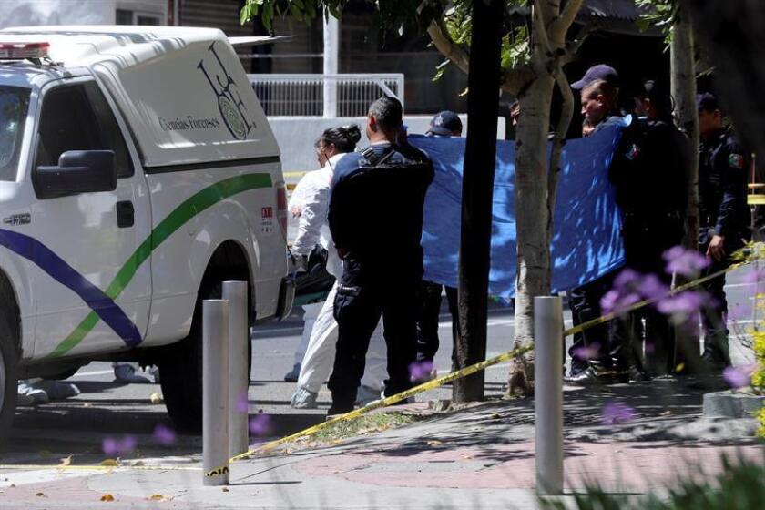 Peritos forenses recaban información en torno al vehículo de lujo donde su conductor fue asesinado mientras circulaba por una avenida de la ciudad de Guadalajara (México) hoy, miércoles 14 de marzo de 2018. EFE