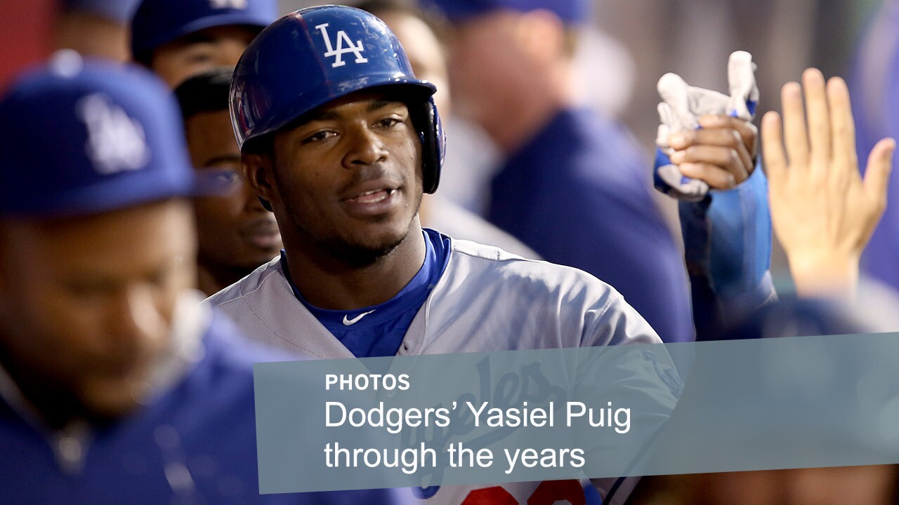 Dodgers center fielder Yasiel Puig is congratulated by teammates after scoring against the Angels during a game in Anaheim last season.