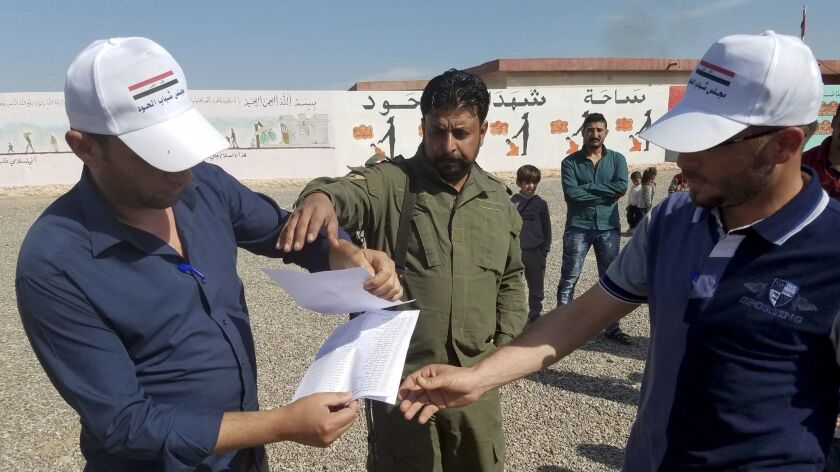 Adil Amash, left, and Hussein Hassan, who have been digging at the mass grave to try to find missing relatives, show Sunni militia member Sgt. Major Yasser Ahmed a list they have compiled of 118 people missing or presumed dead.