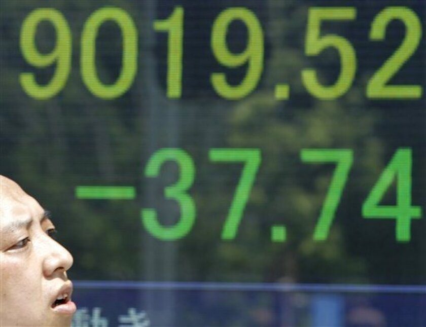 A man walks by an electronic stock board of a securities firm in Tokyo Thursday, Aug. 18, 2011. Japan's benchmark Nikkei 225 fell 37.74 points, or 0.4 percent to 9,019.52 in the morning after the finance ministry said exports fell 3.3 percent from a year earlier to 5.78 trillion yen ($75.6 billion)