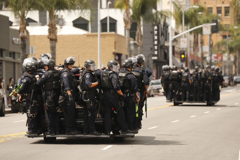 LAPD officers in riot gear drive toward protesters in Hollywood