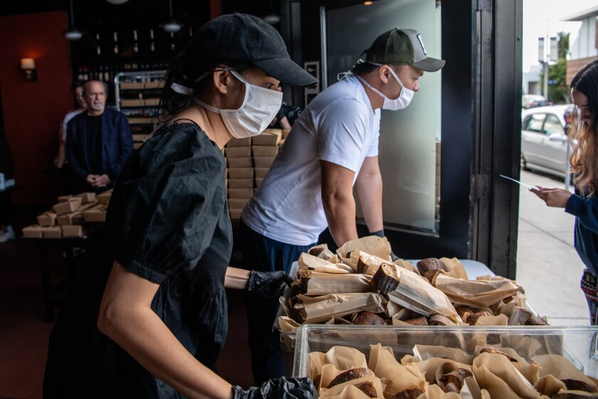 Angelenos line the block outside Chi Spacca on Thursday as Nancy Silverton and her staff distribute 300 free meals to those in the restaurant industry affected by closures because of the coronavirus pandemic.
