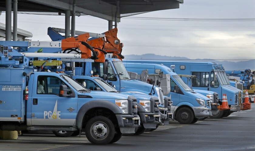 FILE - In this Jan. 14, 2019, file photo, Pacific Gas & Electric vehicles are parked at the PG&E Oakland Service Center in Oakland, Calif. Pacific Gas & Electric on Monday, March 16, 2020, won court approval to raise $23 billion to help pay its bills over destructive California wildfires after Gov. Gavin Newsom dropped his opposition to a financing package designed to help the nation's largest utility get out of bankruptcy. (AP Photo/Ben Margot, File)