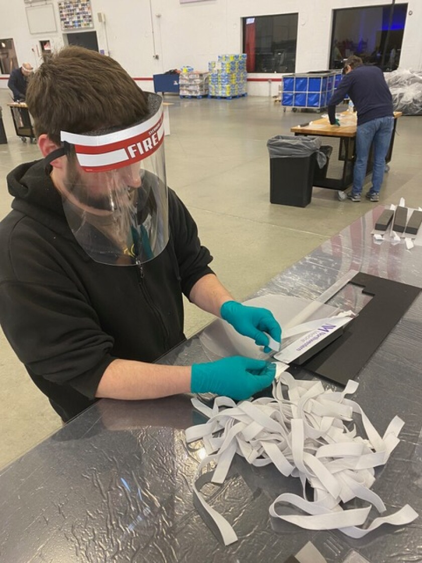 A worker assembles personal protective equipment.