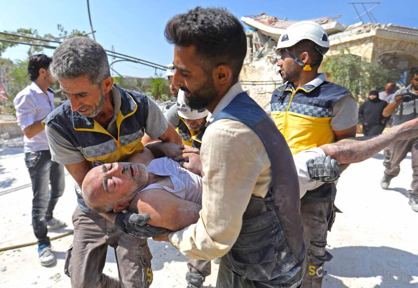 Members of the Syrian Civil Defense carry an injured man after removing him from a building that collapsed during reported airstrikes in the village of Beinin on Tuesday.