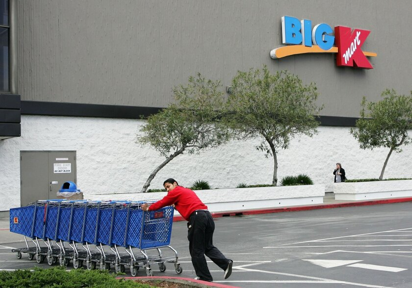 A worker pushes shopping carts through the parking lot of a Kmart store in San Mateo in 2005. The store is one of several the chain is closing.