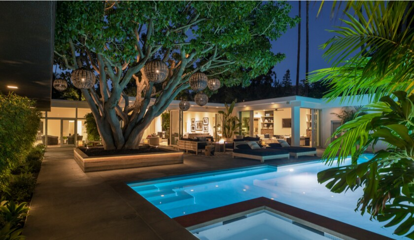 A swimming pool and exterior of a single-story home in Trousdale Estates.