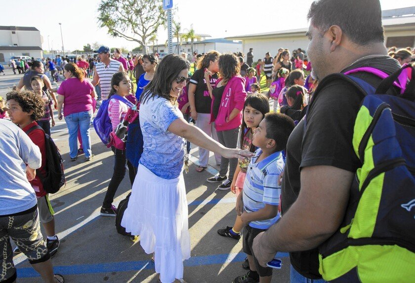 Suzanne Berkers, a third-grade teacher at Oak View Elementary School, talks with students and parents last week on the day Ocean View School District started to bus students from that campus and two others to surrounding districts because of asbestos concerns.