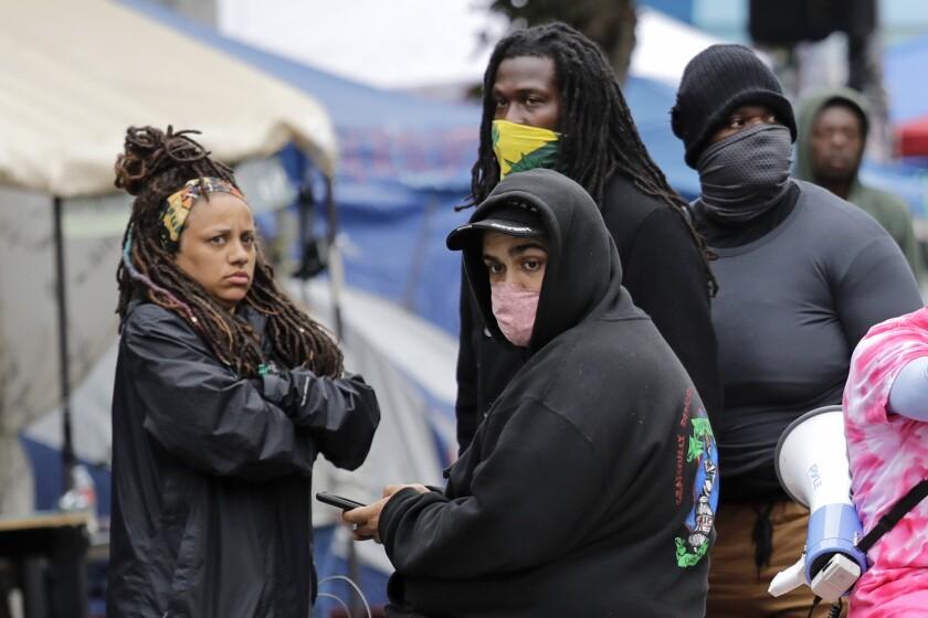 Manifestantes observan mientras la policía de Seattle termina de investigar
