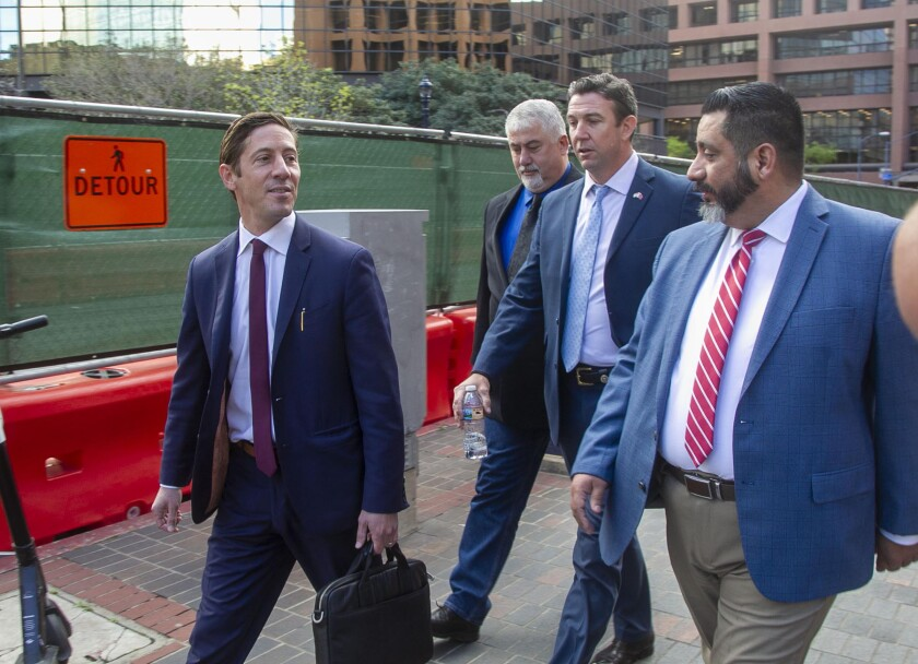 Former U.S. Rep. Duncan Hunter, second from right, leaves the federal courthouse in San Diego.