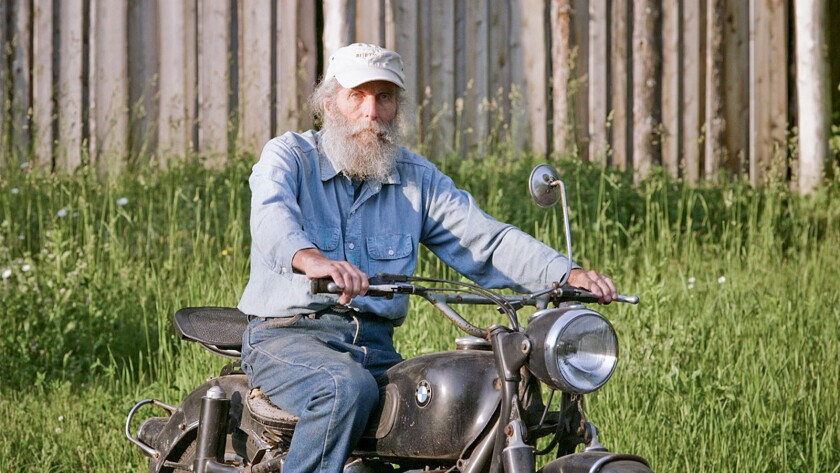 """Burt Shavitz and his vintage motorcycle in a scene from the documentary """"Burt's Buzz."""""""